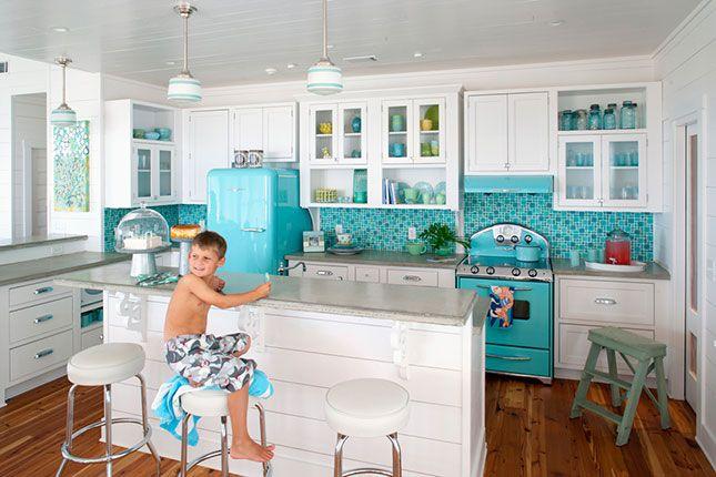Pildil on poiss valges köögis, kus on helesininsed külmkapp, pliit ja köögi taust
