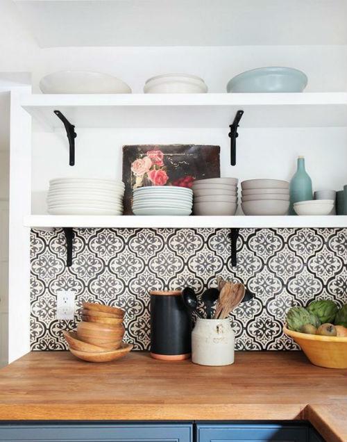 Pildil on köögi töötasapind ja selle taga mustvalge peenikese geomeetrilise mustriga tapeet
