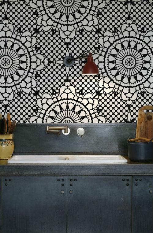 Pildil on tumehall köögimööbel ja taustaks must-valge geomeetrilise mustriga tapeet