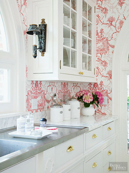 Pildil on valge köögimööbel ja roosade lilledega valge tapeet taustaks