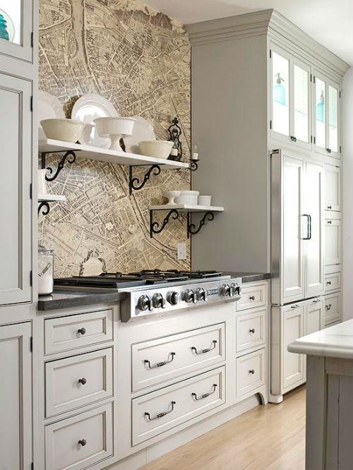 Pildil on helehall köögimääbel ja pliidi taga on taustaks nagu maakaart ja selle peal on veel valged riiulid.