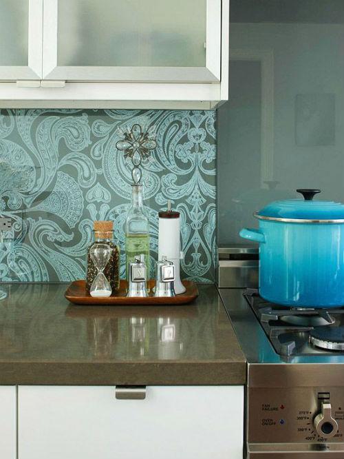 Pildil on rohekas hall lilleline köögi taust pruuni tööpinna ja valge kapiga