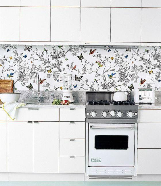 Pildil on valge köögimööbel ja ülemiste ning alumiste kappide vahel tagaseinas on liblikate ja lilledega kirju tapeet