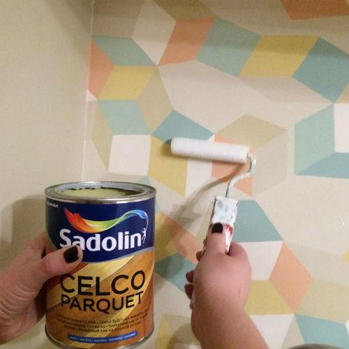 Pildil on värvipurk, käsi värvirulliga ja geomeetrilise mustriga tapeet seinas