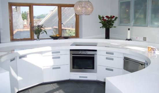 Pildil on ümmarguse, C-kujulise põhiplaaniga valge köögimööbel