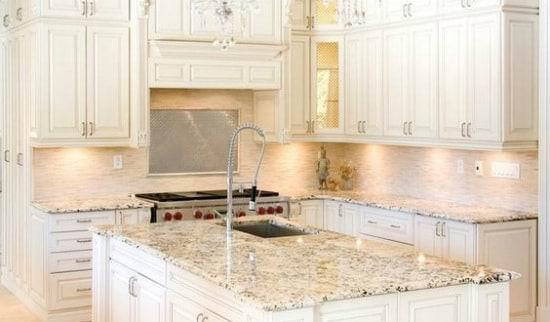 pildil on valge köögimööbel. esiplaanil on köögisaar, millel helehall graniidist tööpind.