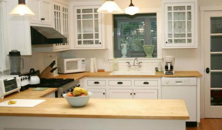 Pildil on esiplaanil täispuidust köögi töötasapind, taga on valged köögikapid