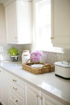 Pildil on valge köögimööbel ja valgest kvartsist tööpind