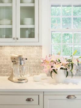 Pildil on otsevaates ja esiplaanil valgest kvartsist tööpind, millel on lilled ja köögikombain
