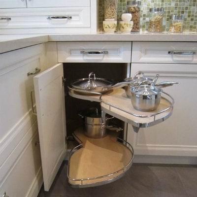 Pildil on valge köögi nurgakapp. Uks on lahti. Uksest liiguvad välja kaks pikergust ovaalset riiulit. Riiulite servas on reeling. Riiulid on tühjad.