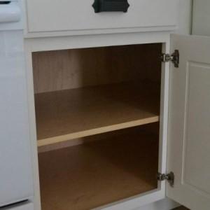 Pildil on lahtise uksega köögikapp. Riiulid on tühjad.