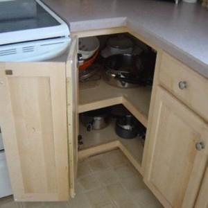 Pildil on avatud ustega täisnurkne nurgakapp. Riiulitelt paistavad kööginõud.
