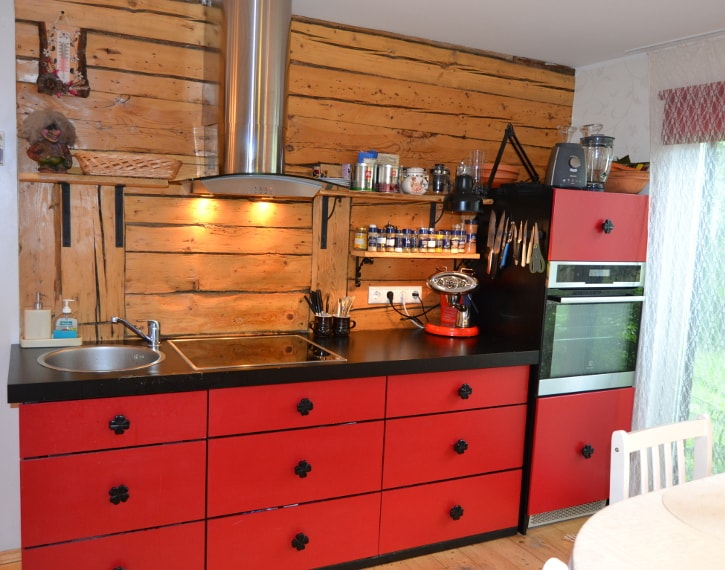 Pildil on punane köögimööbel, must tööpind ja palkidest taustasein. Keskel on kolm sahtliboksi kõrvuti. Pildi paremalpool nende sahtlite kõrval on pisut kõrgem kapp, kus keskel on integreeritud ahi. Kapi alumisel ja ülemisel uksel on kapinupp täpselt ukse keskel.