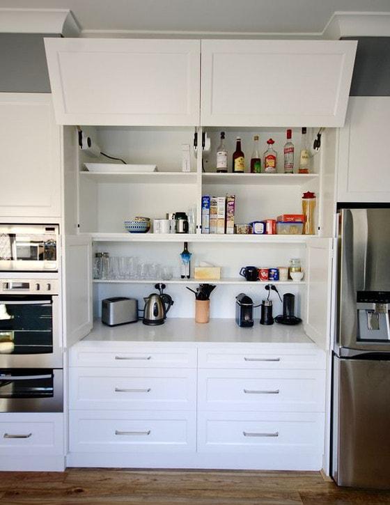 Pildil on valge köögimööbel. Keskel on kaks klaa-ust lahti ning riiulitel paistavad toiduained ja pudelid.