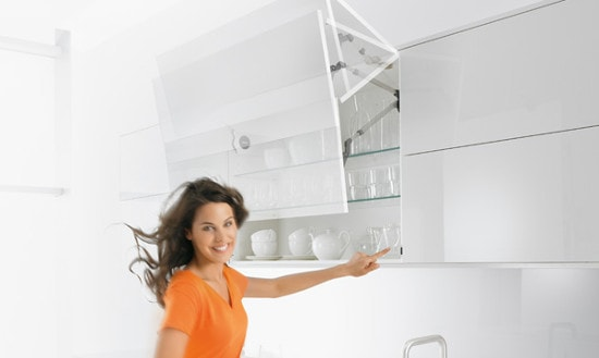 Pildil on valge köögimääbel. Esiplaanil on oranzi pluuusi ja pikkade juustega naine, kes ühe sõrmega vajutab kinni nuppu kapi alumises servas.