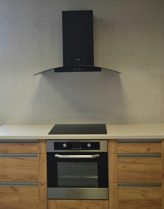 Pildil on helepruun köögimööbel ja must integreeritud ahi, selle peal pliit ning nende kohal seina peal must tagurpidi T-tähe kujuline õhupuhastaja.