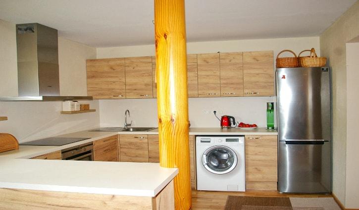 Pildil on helepruun köögimööbel. U-tähe kujulise asetusega. Esiplaanil on kuldkollast värvi puidust ümmargune post, mis on maast kuni laeni. sellest vasakule jääb valge köögi tööpind. Tahapoole jääv köögimööbli seest paistev valge pesumasin ja pildi paremas küljes on hõbehall külmik.