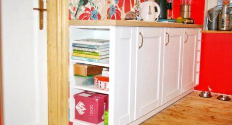 Pildil on valge köögimööbel. Paistab ka punane sein ja põrandal maas on lemmiklooma toidukausid.